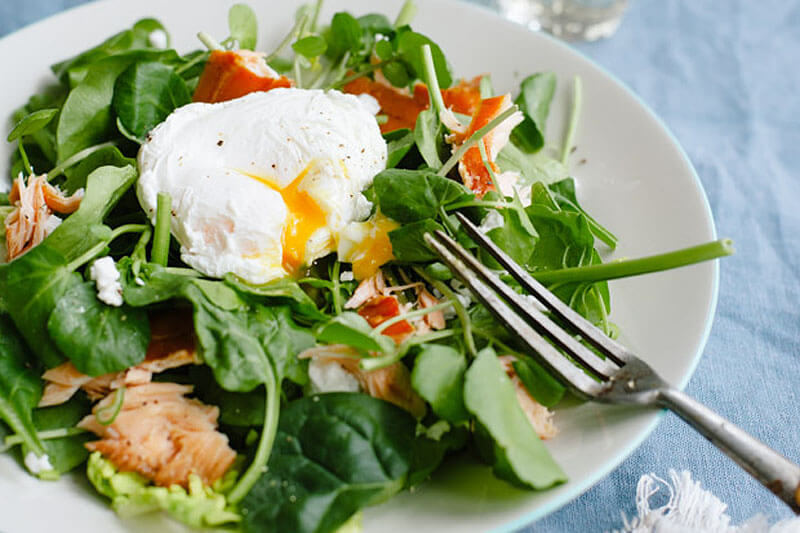 green salad with a poached egg on top