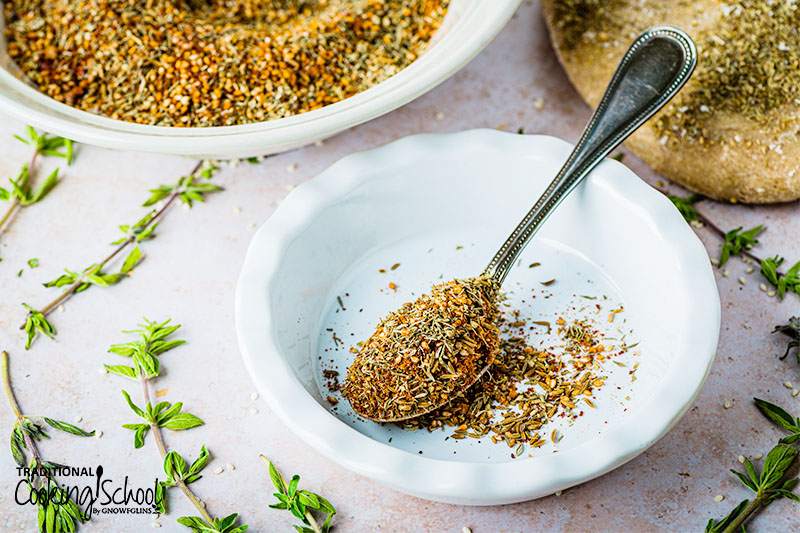 White bowl with a spoon full of za'atar seasoning.
