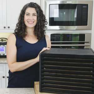 woman smiling in kitchen next to a 9-tray vertical food dehydator
