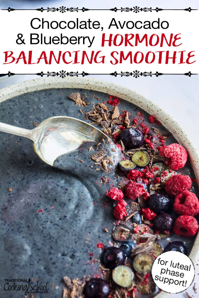 "blue-purple smoothie bowl garnished with blueberries, raspberries, and shaved chocolate. Text overlay: ""Chocolate, Avocado & Blueberry Hormone Balancing Smoothie (for luteal phase support!)"""