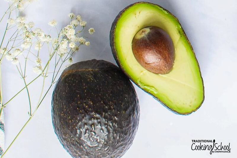 whole avocado next to an avocado half opened to show the pit