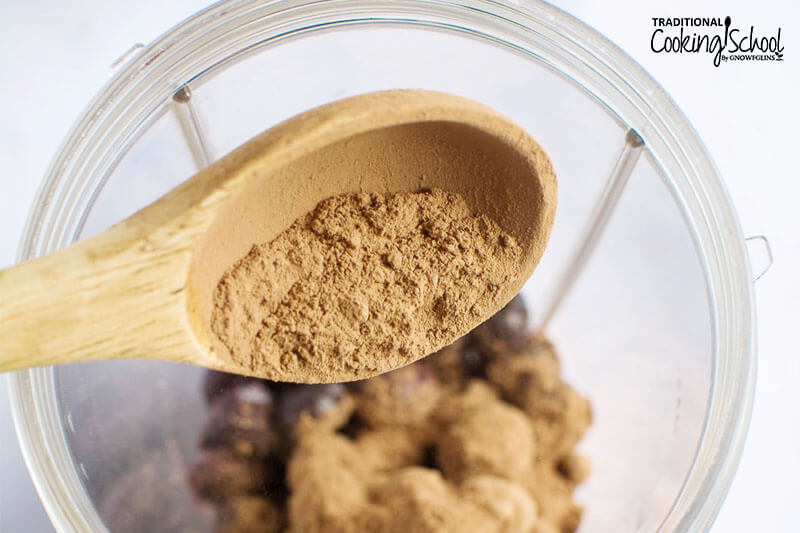 wooden spoon scooping cacao powder into a blender container