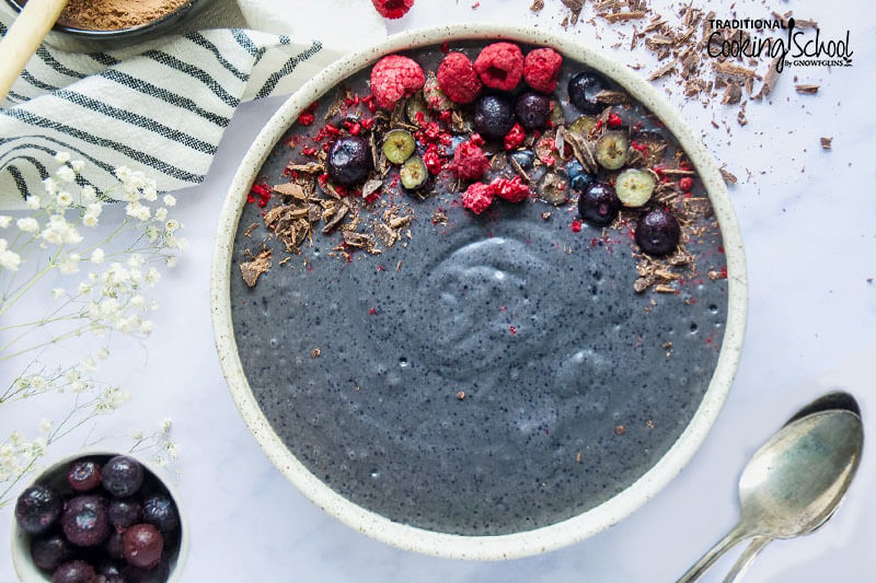 overhead shot of a blue-purple smoothie bowl garnished with berries and shaved chocolate