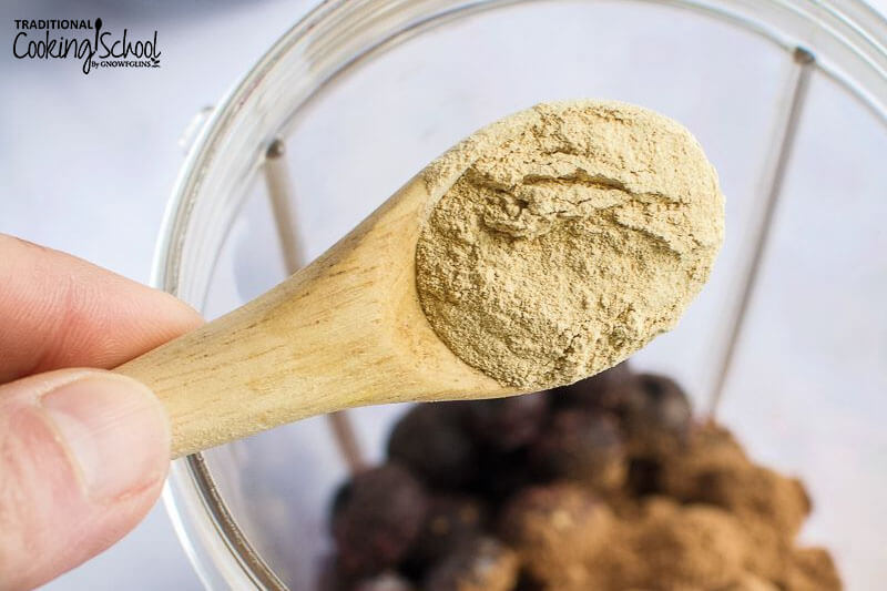 small wooden spoon scooping maca powder into a blender container