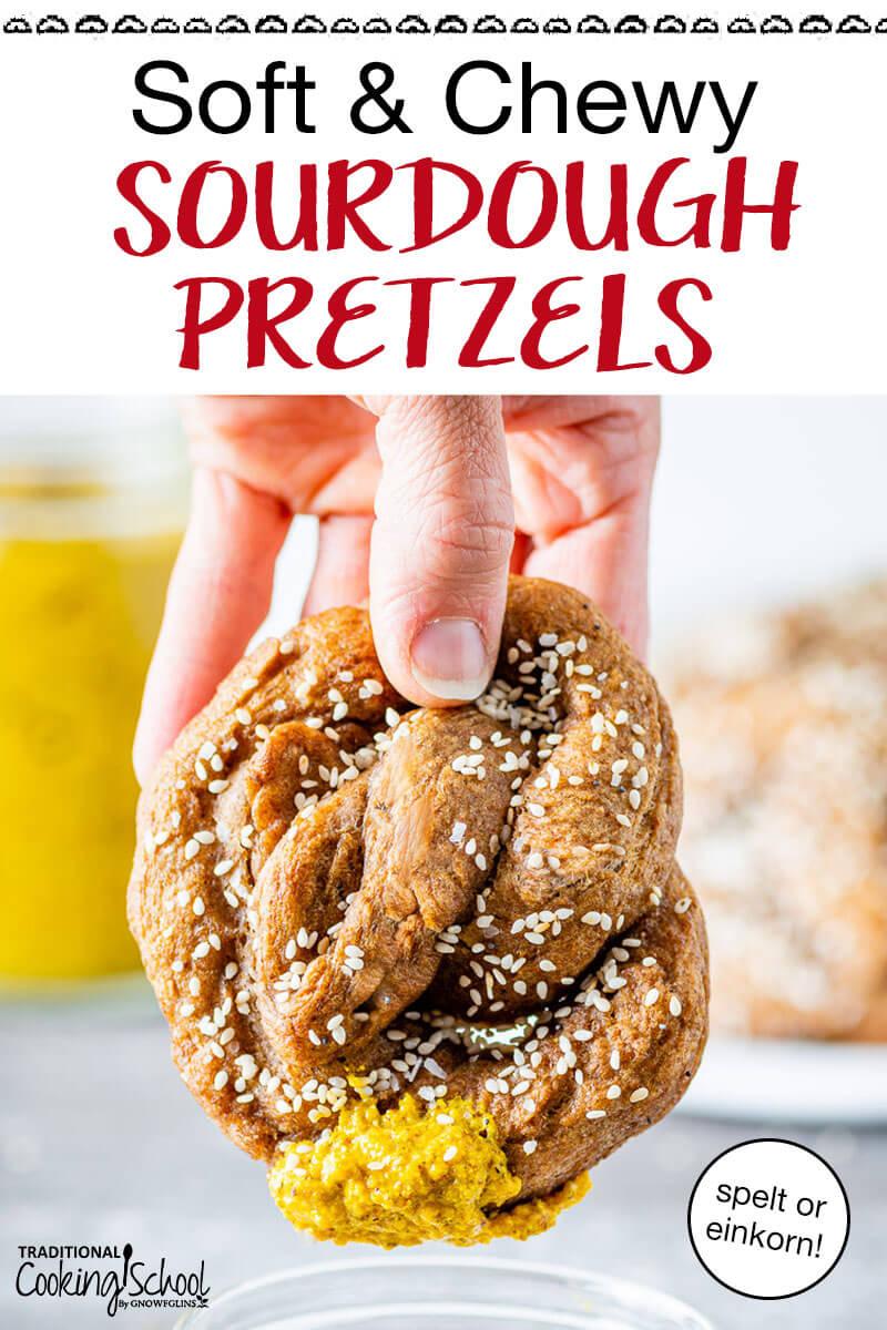 Soft sourdough pretzel being dipped in mustard.
