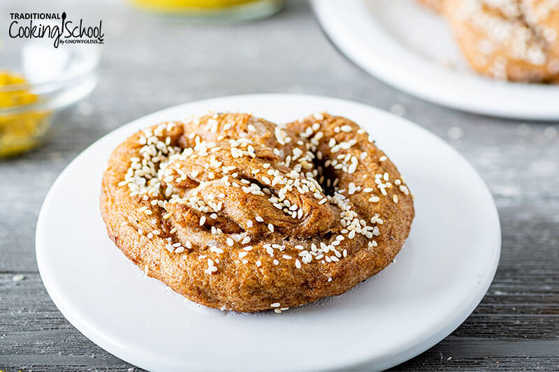 Soft and chewy sourdough pretzel topped with sesame seeds sitting on a white plate.