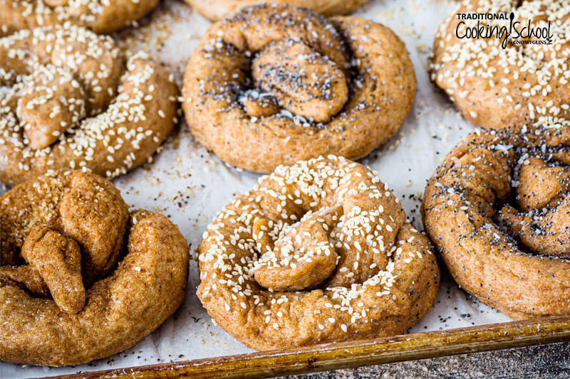 Sourdough pretzels topped with various toppings like poppyseeds, sesame seeds, and cinnamon.