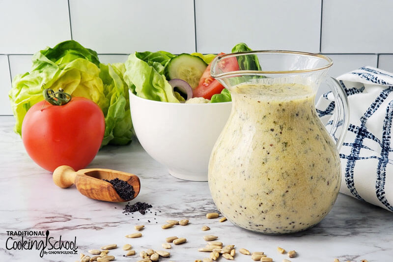 pitcher of creamy, light-colored dressing in front of fresh produce and a green salad