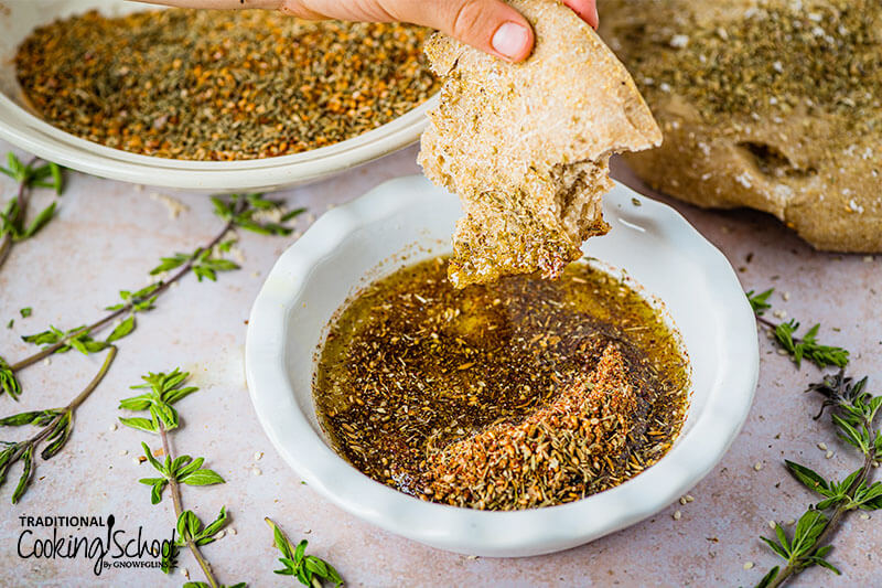Flatbread being dipped into a bowl of olive oil and Za'atar seasoning.