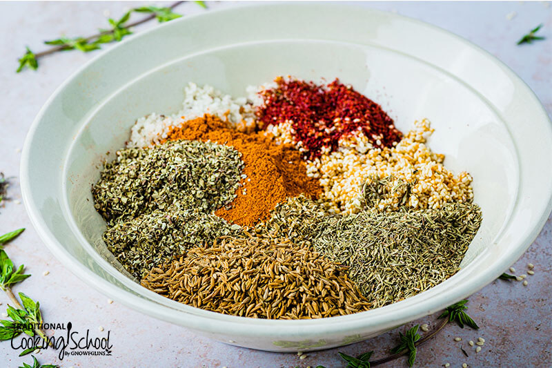 8 different herbs and spices in a white bowl.