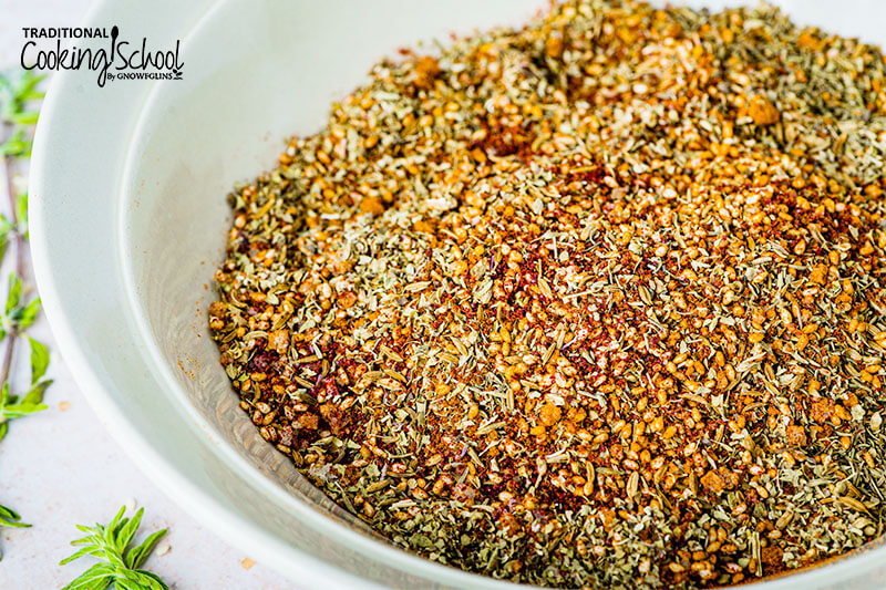 Close up picture of Zatar seasoning in a white bowl.