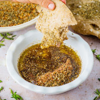 dipping a piece of flatbread in a bowl of zatar and olive oil