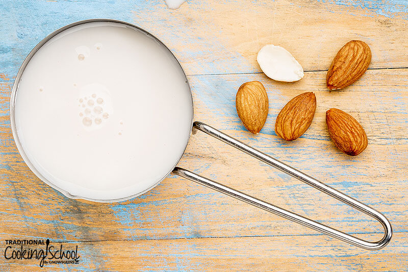 measuring cup of almond milk next to a few scattered almonds