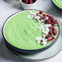 bright green smoothie bowl garnished with coconut, freeze-dried raspberries, and chia seeds
