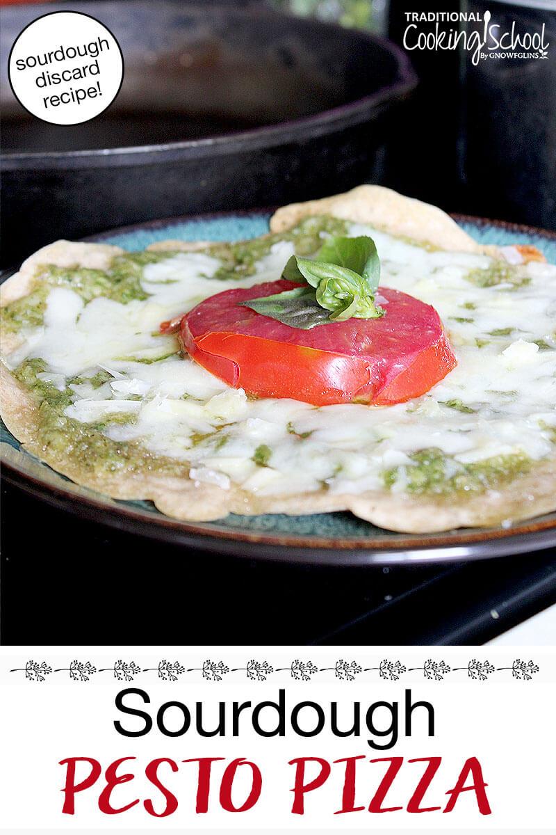 "mini pizza on a plate topped with pesto, melted mozzarella, fresh tomato and basil. Text overlay says: ""Sourdough Pesto Pizza (sourdough discard recipe!)"""