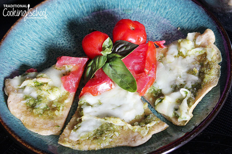 slices of pesto pizza on a plate, garnished with fresh herbs and tomato