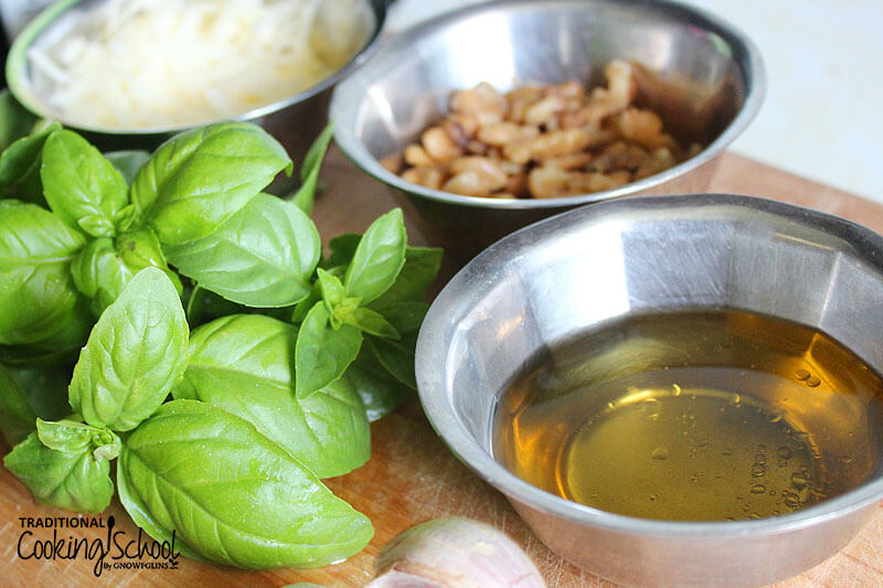 ingredients for making pesto in small stainless steel bowls: fresh basil, walnuts, Parmesan, and olive oil