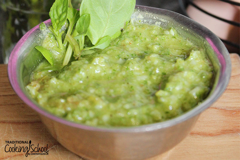 small stainless steel bowl of pesto garnished with fresh basil
