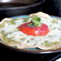mini pizza on a plate topped with pesto, melted mozzarella, fresh tomato and basil