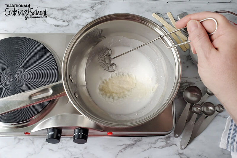 woman's hand whisking together ingredients in a small pot