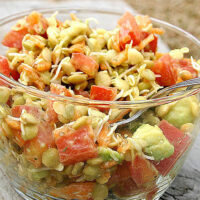 sprouted lentil salad in a clear bowl with tomatoes and avocados