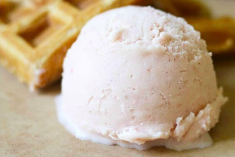 scoop of light pink colored ice cream with a waffle in the background