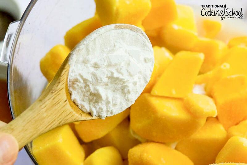 wooden teaspoon adding tapioca flour to frozen mango chunks