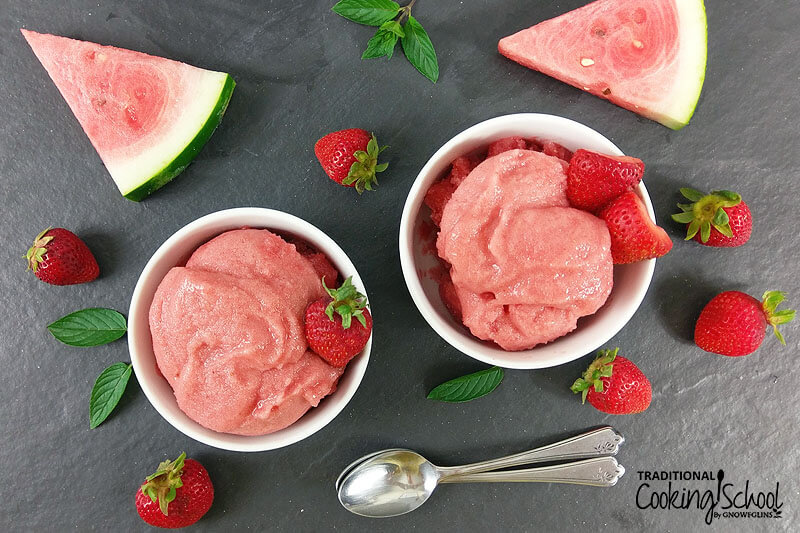 overhead shot of two bowls of pink-colored fruit sorbet garnished with fresh strawberries