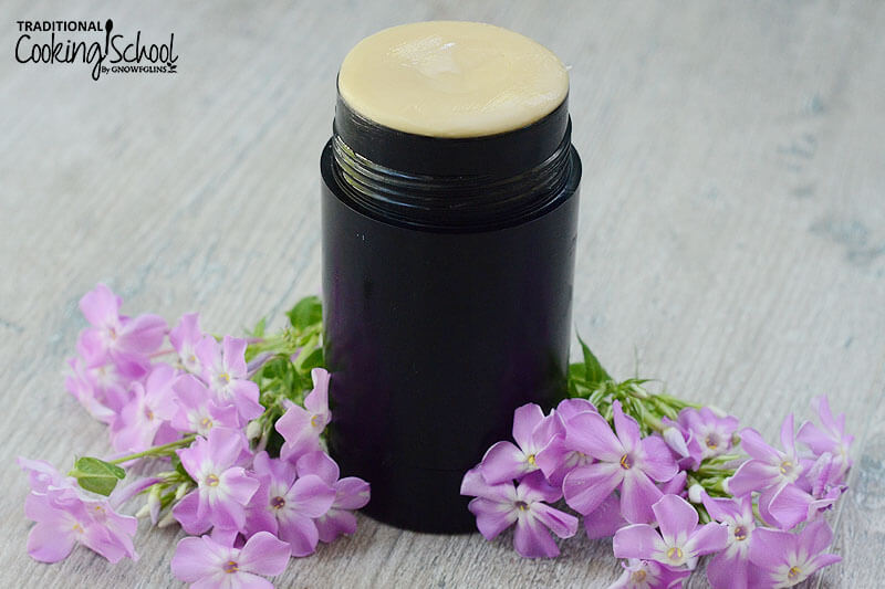 Deodorant stick surrounded by purple flowers.