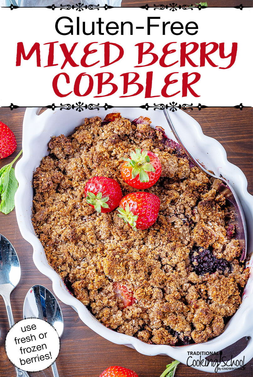 "Cobbler garnished with fresh strawberries in a pretty white ceramic dish with scalloped edges. Text overlay says: ""Gluten-Free Mixed Berry Cobbler (use fresh or frozen berries!)"""