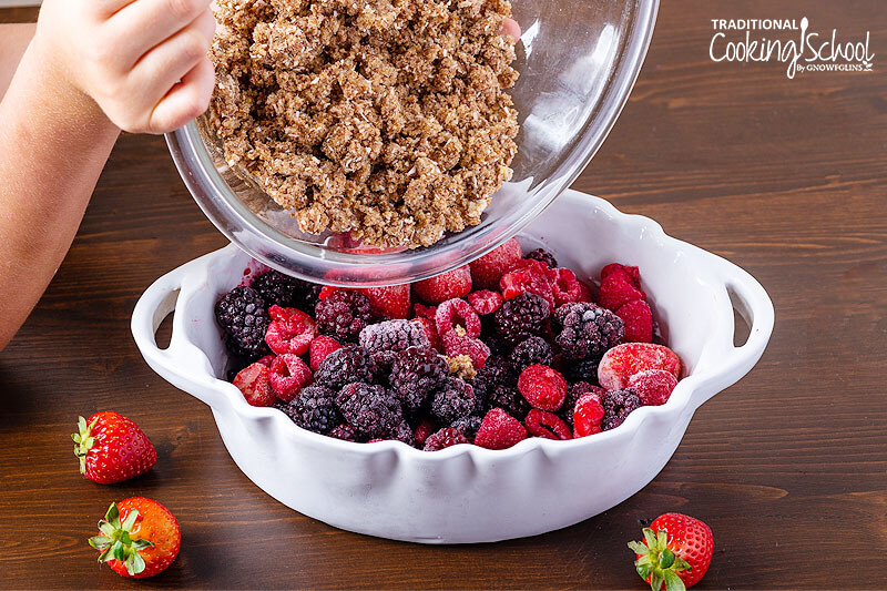 Pouring crumble topping over a casserole dish of frozen berries.
