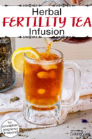 "Amber-colored cold herbal infusion with a lemon slice. Text overlay says: ""Herbal Fertility Tea Infusion (for conception, pregnancy & beyond!)"""