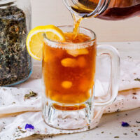 Pouring a cold herbal infusion into a glass to make iced tea. A lemon slice is stuck on the rim of the glass.