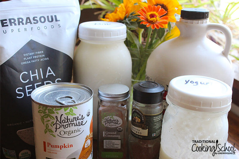 array of ingredients, including maple syrup, chia seeds, yogurt, and pureed pumpkin