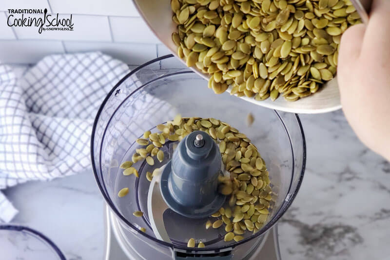 pouring soaked and dehydrated pumpkin seeds into the bowl of a food processor