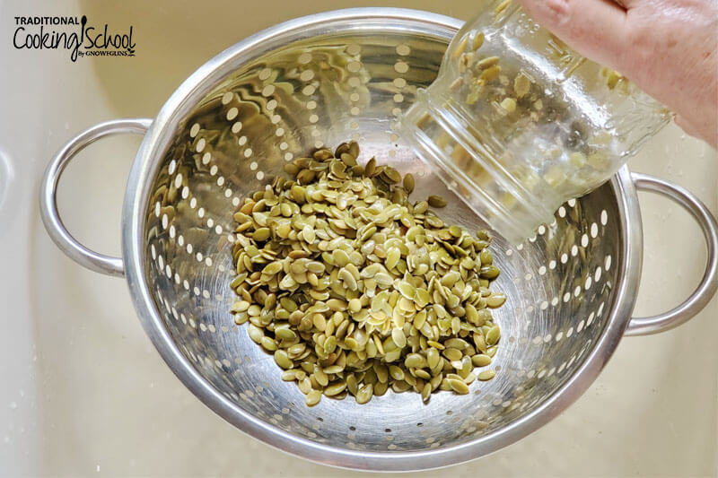 pouring soaked pumpkin seeds into a colander to drain