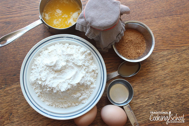 Ingredients for making cinnamon roll dough, including flour, sugar, melted butter, eggs, etc.