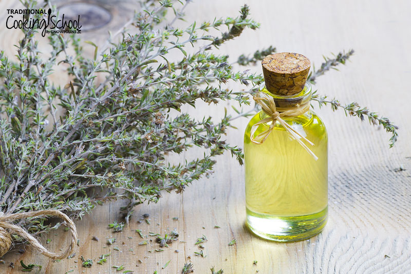 Thyme essential oil in a small bottle next to a bundle of the dried herb.