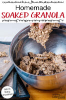 "Woman's hand breaking apart sheets of granola in a stainless steel bowl, next to a stack of dehydrator trays. Text overlay says: ""Homemade Soaked Granola (rich in living enzymes!)"""