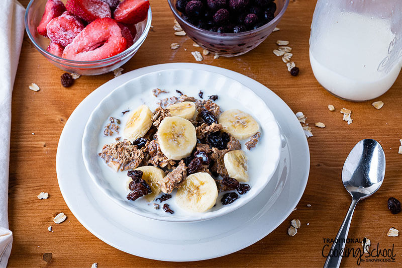 Bowl of homemade granola topped with raisins, banana slices, and milk. Frozen strawberries and blueberries are nearby as additional toppings.