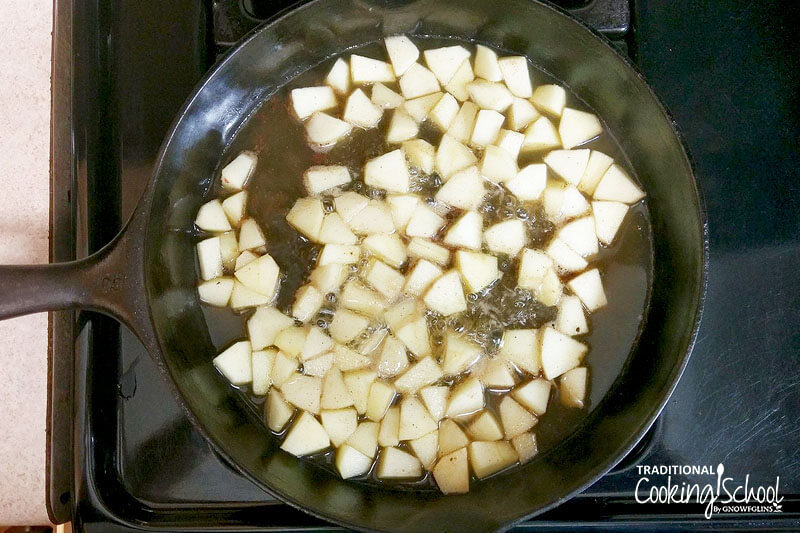 Apple chunks sauteing in a cast iron skillet.