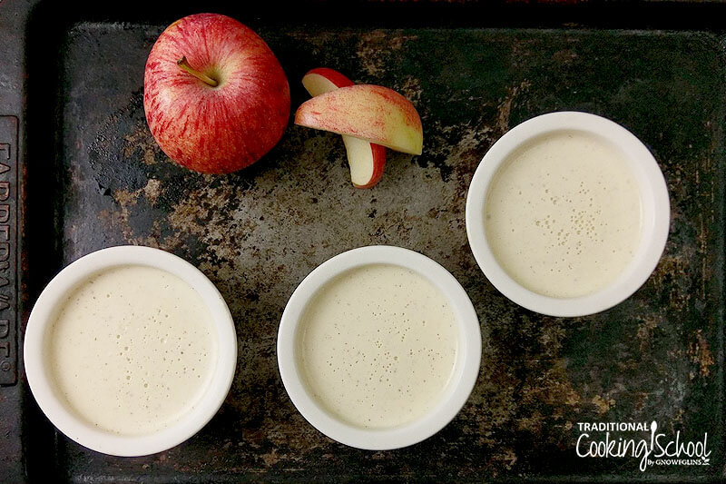Small ceramic bowls of panna cotta on a tray next to an apple.
