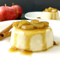 Panna cotta on a plate topped with sauteed apple chunks and a caramel sauce.