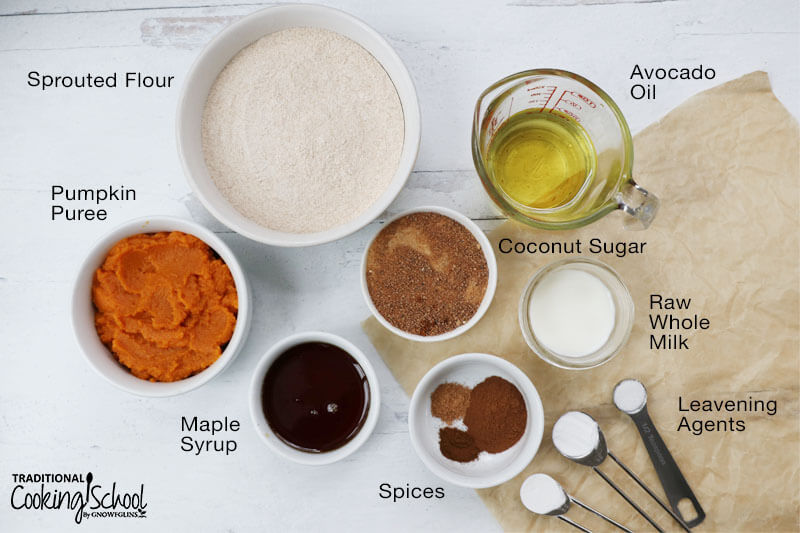 Overhead shot of ingredients for making coffee cake: sprouted flour, pumpkin puree, maple syrup, spices, leavening agents, raw whole milk, coconut sugar, and avocado oil.