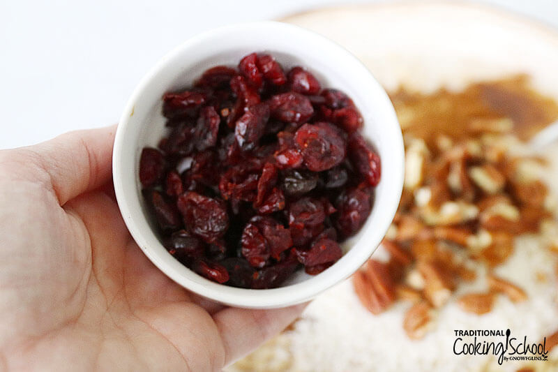 Bowl of dried cranberries in a woman's hand.