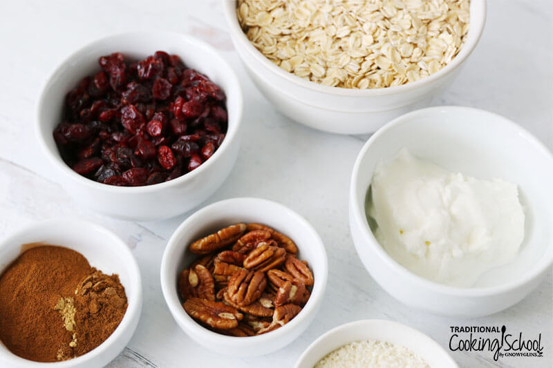 Ingredients for making soaked muesli: rolled oats, yogurt, dried cranberries, pecans, shredded coconut, and a bowl of spices including cinnamon and ginger.