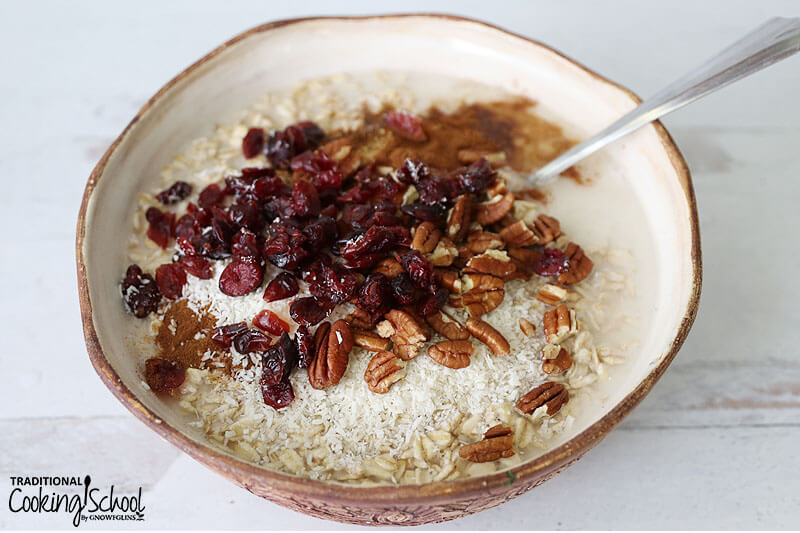 Bowl of muesli topped with dried canberries, cinnamon, shredded coconut, and pecans.
