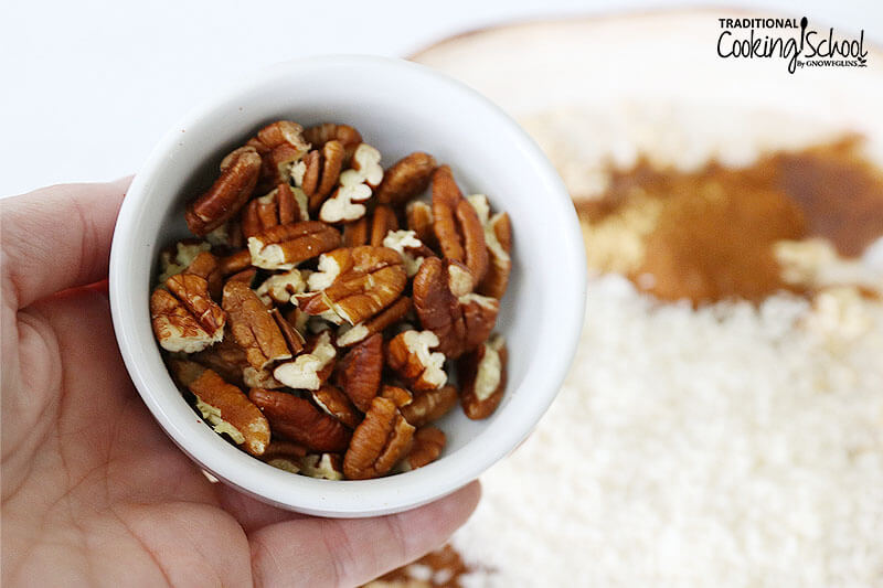 Bowl of pecans in a woman's hand.