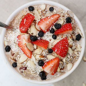 Bowl of muesli topped with fresh strawberries, blueberries, slivered almonds, and shredded coconut.