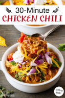 "Bowl of chili topped with sour cream, red onion, cilantro, and grated cheddar cheese, and a ladle spooning more chili over top. Text overlay says: ""30-Minute Chicken Chili (with a kick!)"""